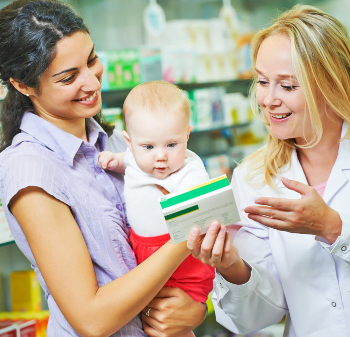 pharmacist talking to a woman adult woman holding a baby